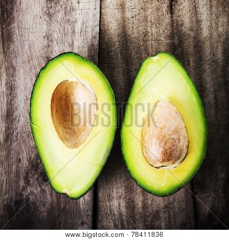 Fresh Avocado Sliced Over Vintage Wooden Background Close Up. Ripe Green Avocado Fruit On Wood Board