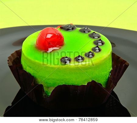Delicious Green Cake With Cherry On Black Plate On Green Background