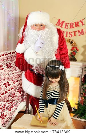 Little cute girl writing letter to Santa Claus near Christmas tree at home