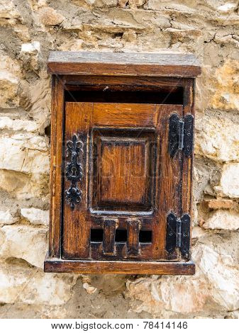 age letter box made of wood on a house wall