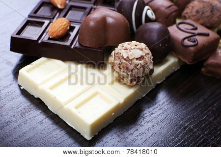 Bars of white and bitter chocolates with candies, cinnamon stick and almond on the dark wooden smooth background