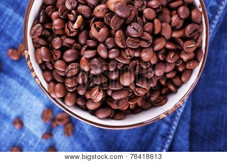 bowl of coffee beans stands on jeans background