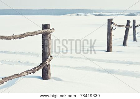 Old wooden fence in snow