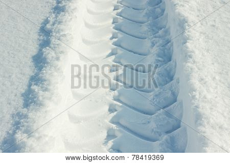 Tire tracks in fresh snow on a sunny day