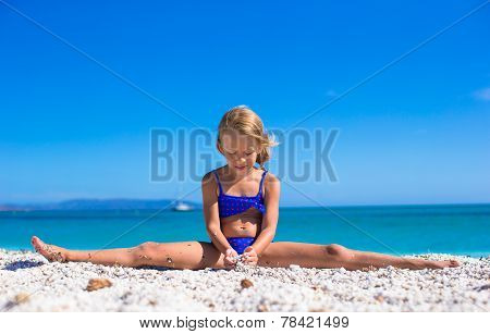 Adorable little girl making leg-split on tropical white sandy beach and enjoying summer vacation