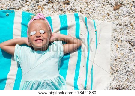 Adorable little girl have fun on towel at white beach