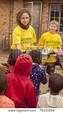 two volunteer aid workers handing out Christmas gifts to underprivileged children in South Africa.