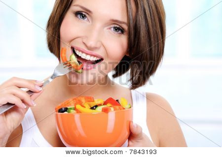 Cheerful Female Eats Vegetable Salad