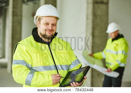 young male construction engeneer worker project manager with tablet pc at a indoors building site