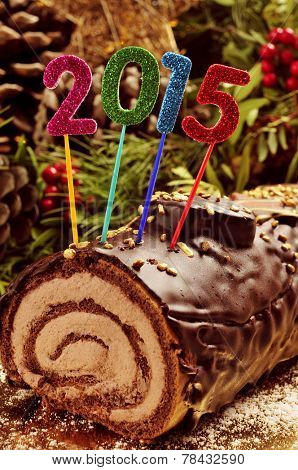 a yule log cake, traditional of christmas time, with glittering numbers of different colors forming the number 2015, as the new year