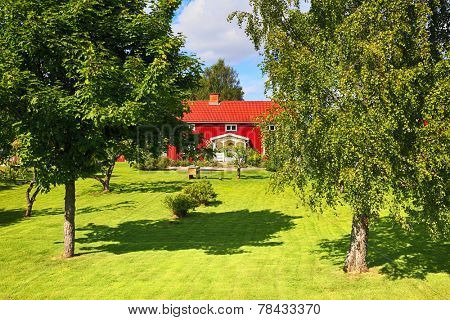 old red house in a lush green garden, summer time in Sweden