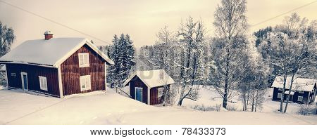 old cottages in a rural snowy winter landscape typical of Sweden
