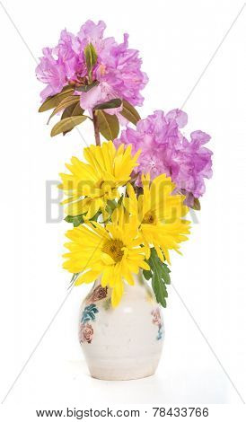 A spring bouquet of yellow mums and lavender PJM rhodoendrons in a ceramic vase.