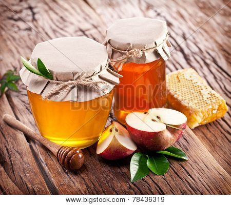 Glass cans full of honey, apples and combs on old wooden table.