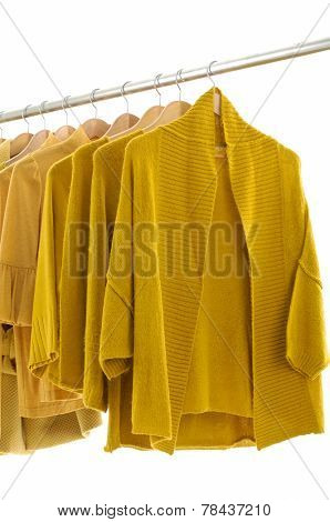 female yellow jacket and clothes hanging on clothes rack
