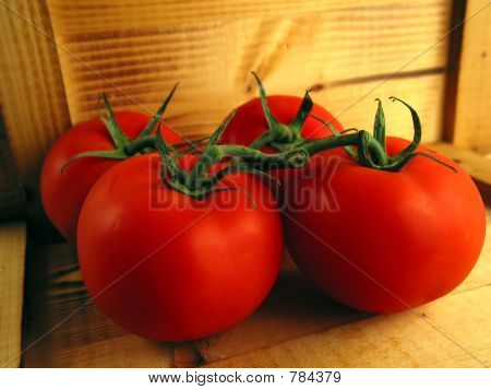 4 tasty red tomatoes on wood
