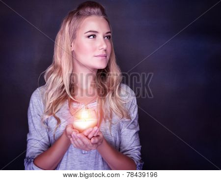 Portrait of beautiful blond girl with glowing candle in hands on dark background, praying on Christmas time, traditional Christian holiday