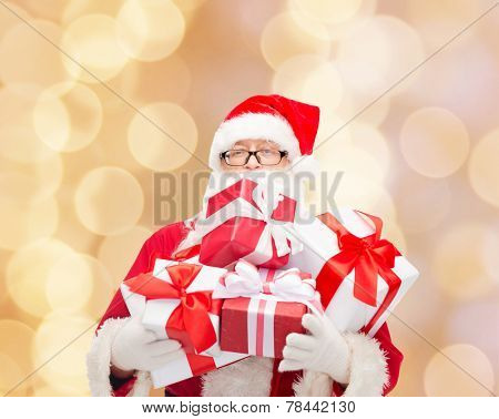 christmas, holidays and people concept - man in costume of santa claus with gift boxes over beige lights background