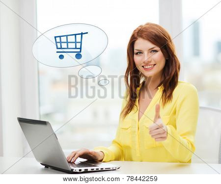 leisure, people, online shopping, gesture and technology concept - smiling young woman with laptop computer and trolley icon showing thumbs up at home