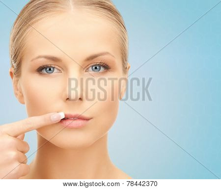 beauty, people and health concept - beautiful young woman pointing finger to her lips over blue background