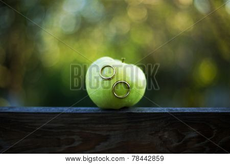 Wedding Rings In A Green Apple