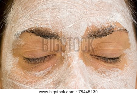 Woman closed eyes and forehead with mudpack, front view