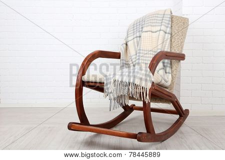 Rocking chair covered with plaid on wooden floor near the brick wall background