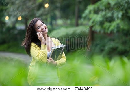 Beautiful young female university student with books and files in arm, using her phone, standing in a park.