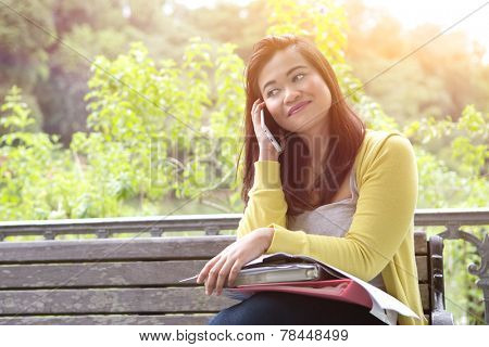 Beautiful young female university or college student reading ?a book, seated by a lake in a park.