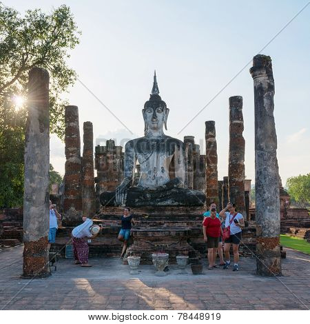 Tourists Near Buddha Statue In Old Buddhist Temple Ruins