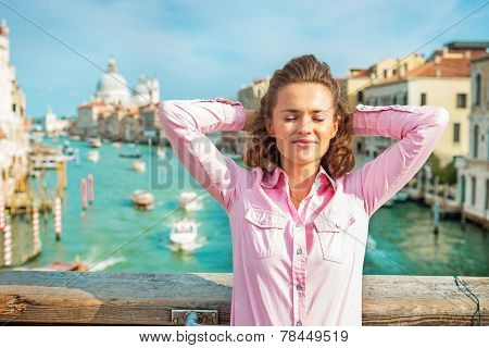Relaxed Young Woman Standing On Bridge With Grand Canal View In