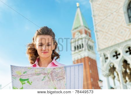 Portrait Of Young Woman Looking At Map Against Campanile Di San