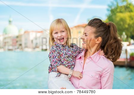 Portrait Of Happy Mother And Baby Standing On Grand Canal Embankment In Venice, Italy