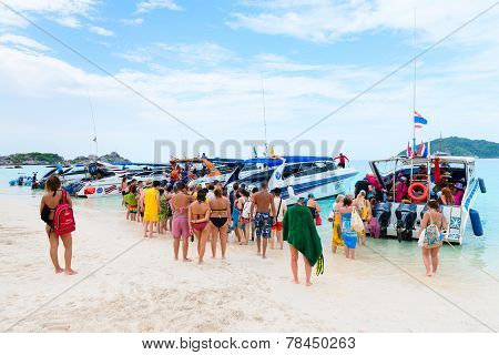 Tourists Go On Board The Speed Boat On The Beach