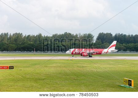 Airplane of AirAsia low-cost airline taxis in airport
