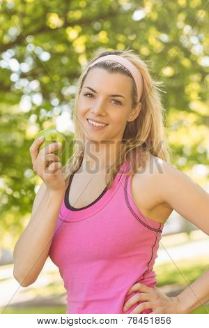 Fit blonde holding green apple on a sunny day