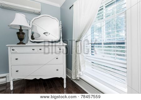 White painted dresser with mirror and lamp near window interior