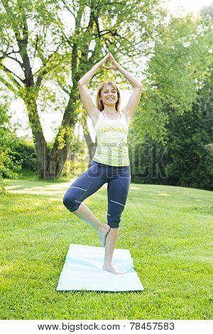 Female fitness instructor doing yoga tree or vrksasana pose in green park