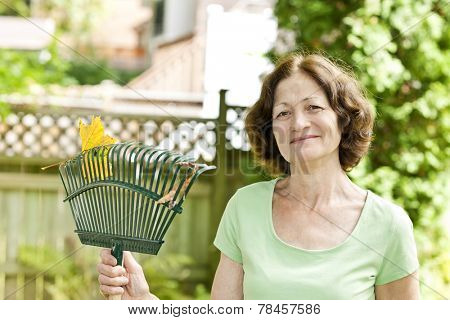 Senior woman smiling holding rake for yard work outside