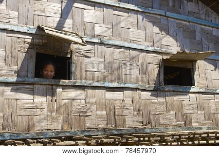Woman looks from the windows of her house, Bandarban, Bangladesh.