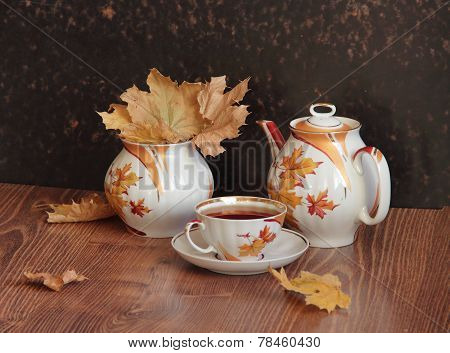 Still-life with tea and a bouquet from autumn leaves
