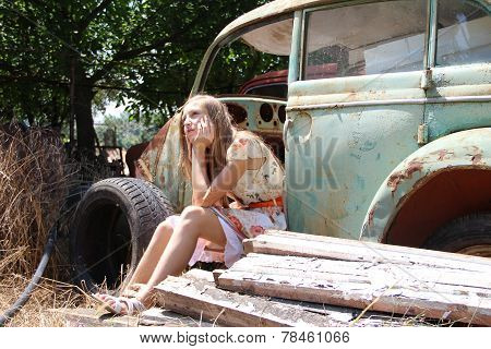 pensive country girl from an old broken car