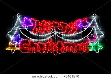 Merry Christmas in lights on brick wall