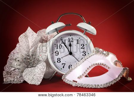 Happy New Year Clock, Masquerade Party Mask And Festive White Flowers On Ared Background.