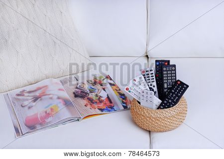 Many remote control devices on sofa