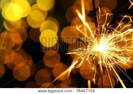 Beautiful sparkler on shiny background, close up