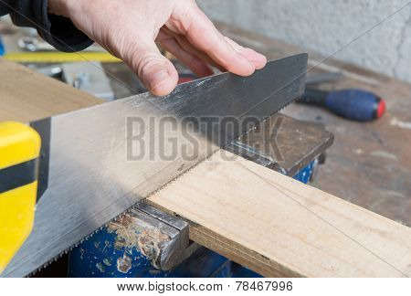 A Worker Cut A Plank Of Wood With A Hand Saw