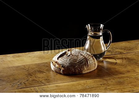A Loaf Of Bread And A Jug Of Water On Wooden Table