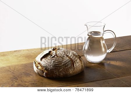 A Loaf Of Bread And A Jug Of Water On Table