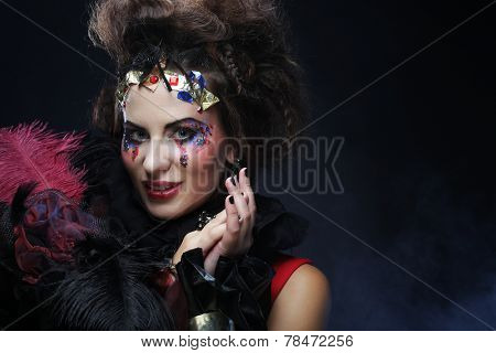 portrait of woman with artistic make-up in blue smoke, party theme